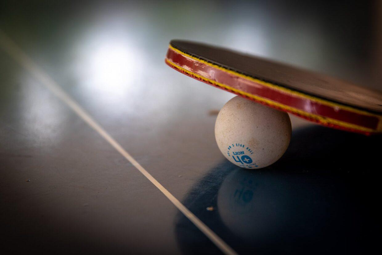 ping pong ball and racket on black table